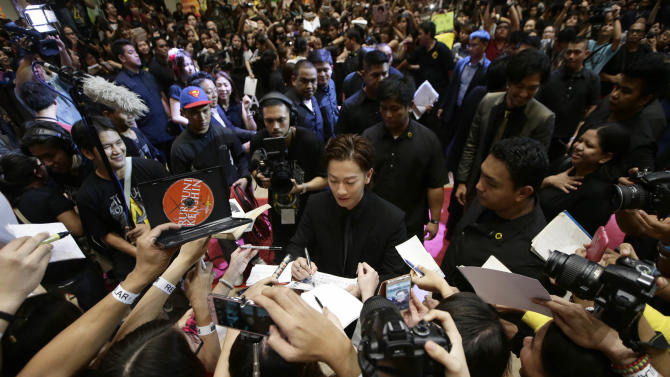 """Japanese actor Takeru Satoh, centre, signs autographs, prior to the premiere screening of the Japanese film """"Rurouni Kenshin"""" at a mall cinema, in Mandaluyong city, east of Manila, Philippines Wednesday, Aug. 6, 2014. """"Rurouni Kenshin"""" is the second live action film and the first to be premiered outside Japan. (AP Photo/Bullit Marquez)"""