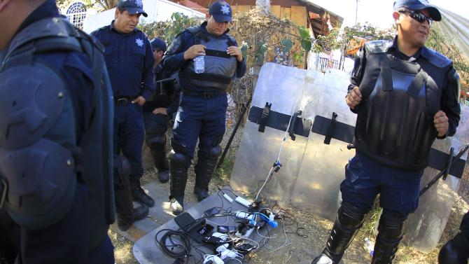 Federal police officers charge their mobile phones on a shield as they stand guard on the streets near the attorney general's office in Chilpancingo, in the Mexican state of Guerrero