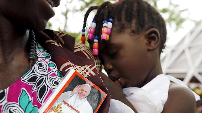 A woman carries a child as Pope Francis leads a mass in Kampala
