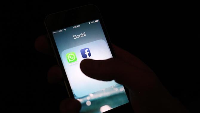This Wednesday, Feb. 19, 2014 photo, shows the WhatsApp and Facebook app icons on an iPhone in New York. On Wednesday Facebook announced it is buying mobile messaging service WhatsApp for up to $19 billion in cash and stock. (AP Photo/Karly Domb Sadof)