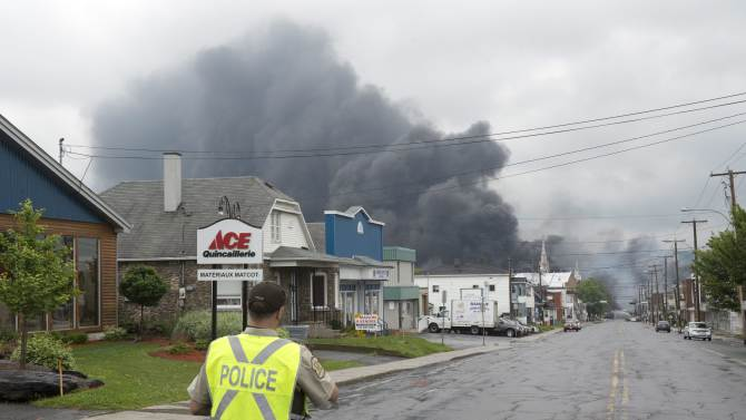 A police officer watches as smoke rises from railway cars that were carrying crude oil after derailing in downtown Lac Megantic, Que., Saturday, July 6, 2013. A large swath of Lac Megantic was destroyed Saturday after a train carrying crude oil derailed, sparking several explosions and forcing the evacuation of up to 1,000 people. (AP Photo/The Canadian Press, Paul Chiasson)
