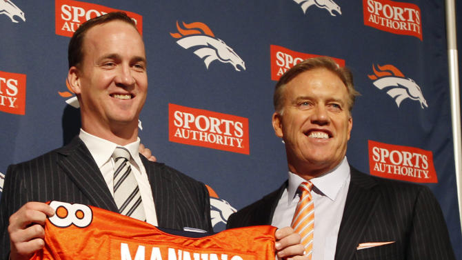 FILE - In this March 20, 2012, file photo, Denver Broncos executive vice president of football operations John Elway, right, and new quarterback Peyton Manning smile during an NFL football news conference at the team's headquarters in Englewood, Colo. Elway is turning the Broncos into winners again. As recently as two years ago, they were dissolving into irrelevance. (AP Photo/David Zalubowski, File)