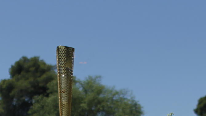 Greek swimming champion Spyros Gianniotis, the first torchbearer of the Olympic torch relay, carries the olympic flame  in the final dress rehearsal for the lighting of the flame held on Wednesday. May 9, 2012, in Ancient Olympia, Greece. The flame to be lit in Thursday's ceremony in the birthplace of the Ancient Olympics will travel to London, where the Summer Games will take place from July 27-Aug. 12. (AP Photo/Kostas Tsironis)