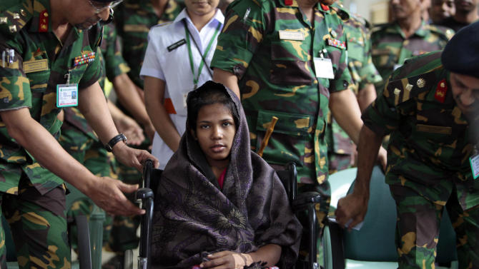 """Reshma Begum, center, the 19-year-old seamstress who spent 17 days trapped in the rubble of a collapsed factory building talks to the media at a hospital in Savar, near Dhaka, Bangladesh, Monday, May 13, 2013. Begum spoke to reporters Monday from the hospital where she is being treated. She told them she never expected to be rescued alive, and she vowed, """"I will not work in a garment factory again.""""  (AP Photo/A.M. Ahad)"""