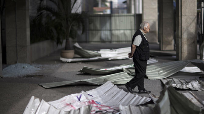 A man walks near the entrance of a commercial building that was damaged during protests in Rio de Janeiro, Brazil, Friday, June 21, 2013. Police and protesters fought in the streets into the early hours Friday as Brazilians swarmed through Brazilian cities in the biggest demonstrations yet against a government viewed as corrupt at all levels and unresponsive to its people. President Dilma Rousseff called an emergency meeting of her top Cabinet members for Friday morning, more than a week after the protests began. (AP Photo/Felipe Dana)