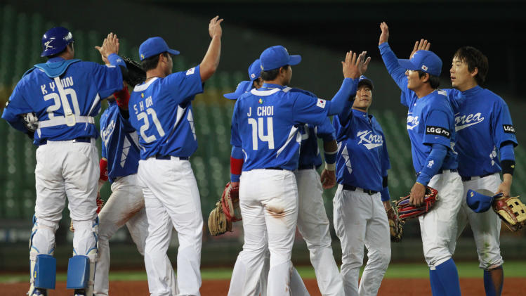 Korea's team congratulates each other on the pitcher's mound after beating Australia 6-0 in their World Baseball Classic first round game at the Intercontinental Baseball Stadium in Taichung, Taiwan, Monday, March 4, 2013. (AP Photo/Wally Santana)