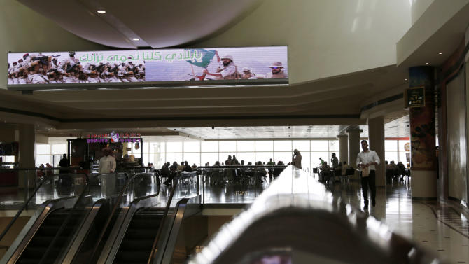 In this photo taken Wednesday, April 15, 2015, shoppers stroll through a mall in Riyadh, Saudi Arabia beneath an electronic billboard supporting the Saudi-led coalition's military action in Yemen.  The message is directed at the Iranian-allied Shiite rebels in Yemen who have been the target of a three-week Saudi-led air campaign. The nationalist fervor whipped up by the war has put calls for reform in the kingdom on hold as people rally behind their king, the troops and the status quo. Billboard reads in Arabic 'My nation we're all here to protect your soil'.  (AP Photo/Hasan Jamali)