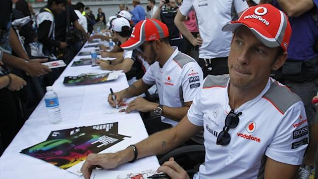 McLaren Formula One driver Jenson Button of Britain (R) and team mate Lewis Hamilton (C) sign autographs at the Buddh International Circuit in Greater Noida (Reuters)