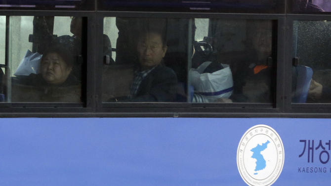 South Koreans look out a bus window upon their arrival from the North Korean city of Kaesong at the customs, immigration and quarantine office near the border village of Panmunjom, which has separated the two Koreas since the Korean War, Tuesday, April 9, 2013. A few hundred South Korean managers, some wandering among quiet assembly lines, were all that remained Tuesday at the massive industrial park run by the rival Koreas after North Korea pulled its more than 50,000 workers from the complex. Others stuffed their cars full of goods before heading south across the Demilitarized Zone that divides the nations. (AP Photo/Lee Jin-man)