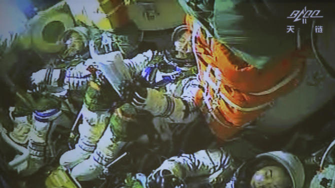 In this photo released by China's Xinhua News Agency, the screen at the Beijing Aerospace Control Center in Beijing shows three astronauts having prepared for the return of the Shenzhou 10 spacecraft to earth on Wednesday, June 26, 2013. The space capsule with three astronauts has safely landed on grasslands in northern China after a 15-day trip to the country's prototype space station. (AP Photo/Xinhua, Wang Yongzhuo) NO SALES