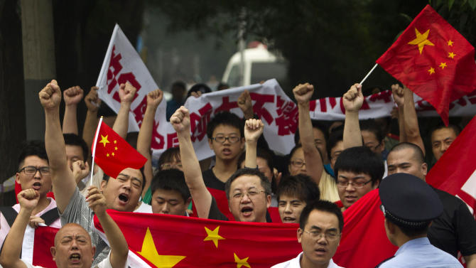 FILE - In this Aug. 18, 2012 file photo, anti-Japan protesters shout slogans while marching with Chinese national flags and banners towards the Japanese Embassy in Beijing, China. Chinese government's sensitivity over protests that took place in several Chinese cities on Aug. 19 over the set of islands, known as Diaoyu in China and Senkaku in Japan, reflects its perpetual fear that allowing its people too much freedom to hold protests, any protests, could snowball into domestic dissidence. (AP Photo/Alexander F. Yuan, File, File)
