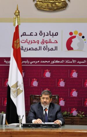 """In this image released by the Egyptian Presidency, Egyptian President Mohammed Morsi speaks at a conference on women's rights held at the Presidential palace in Cairo, Egypt, Sunday, March 24, 2013. Egypt's president delivered a stern warning to his opponents on Sunday, saying he may be close to taking unspecified measures to """"protect this nation"""" two days after supporters of his Muslim Brotherhood and opposition protesters fought street battles in the worst bout of political violence in three months. (AP Photo/Egyptian Presidency)"""