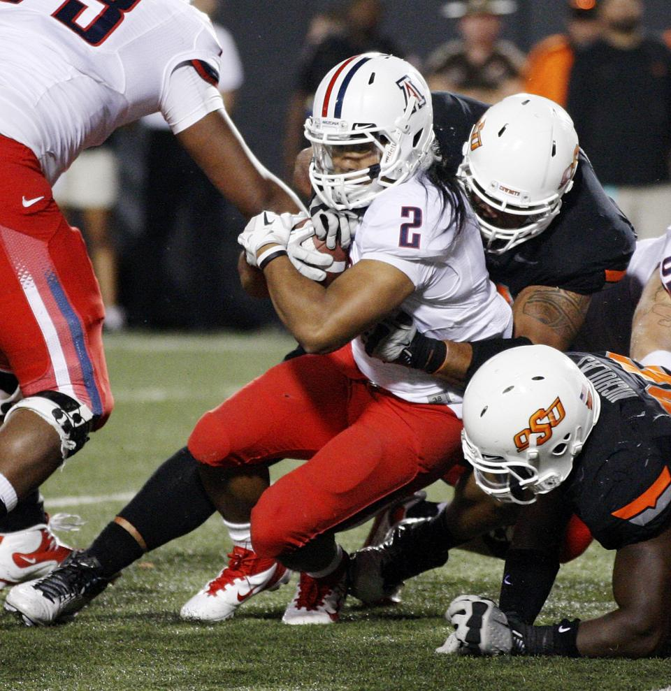 Arizona running back Keola Antolin, left, is stopped by an Oklahoma State defender in the second quarter of an NCAA college football game in Stillwater, Okla., Thursday, Sept. 8, 2011. (AP Photo/Sue Ogrocki)
