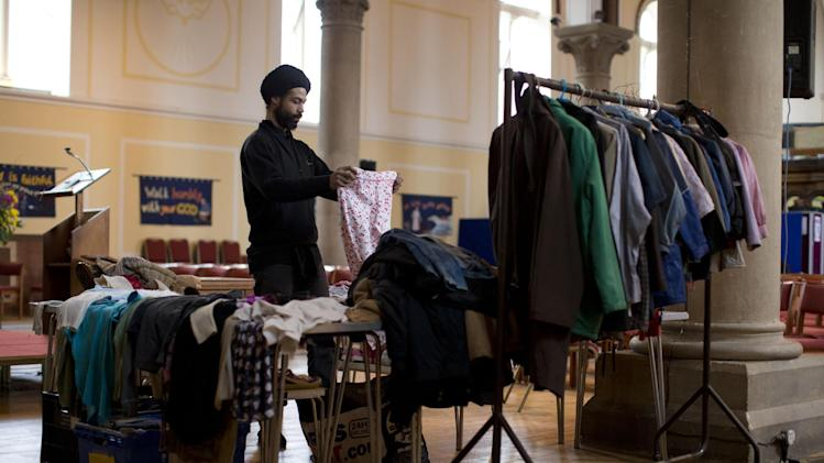 "In this photo taken Friday, April 5, 2013, Christophe, a volunteer from France, arranges items of clothing to give to people at a food bank in St Luke's Church in the West Norwood area of London, Friday, April 5, 2013. It's possible that official figures on first quarter economic growth, to be released Thursday, could put the country back in recession. It would take the smallest statistical variation to put the figure in negative territory which would place the country in recession, another recession _ the third since the 2008 financial crisis _ and is already being referred to with foreboding in the media as a ""Triple Dip"". (AP Photo/Matt Dunham)"