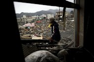 A tsunami survivor clears her house of debris, as she looks for her mother and brother believed to be burried under the debris in the tsunami-damaged town of in Otsuchi, in Iwate prefecture. Radiation levels have surged in seawater near a tsunami-stricken nuclear power station in Japan, officials said Saturday, as engineers battled to stabilise the plant in hazardous conditions