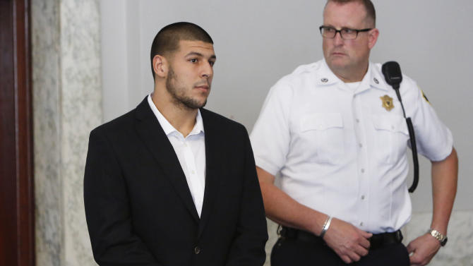 Former New England Patriots NFL football tight end Aaron Hernandez, left, appears at Attleboro District Court on Wednesday, July 24, 2013, in Attleboro, Mass. Hernandez has pleaded not guilty to murder in the death of Odin Lloyd. Hernandez was in court for what was supposed to be a probable cause hearing, but prosecutors said the grand jury is still considering the evidence against him. A judge rescheduled the probable cause hearing for Aug. 22, after considering defense objections to a delay. (AP Photo/Bizuayehu Tesfaye)