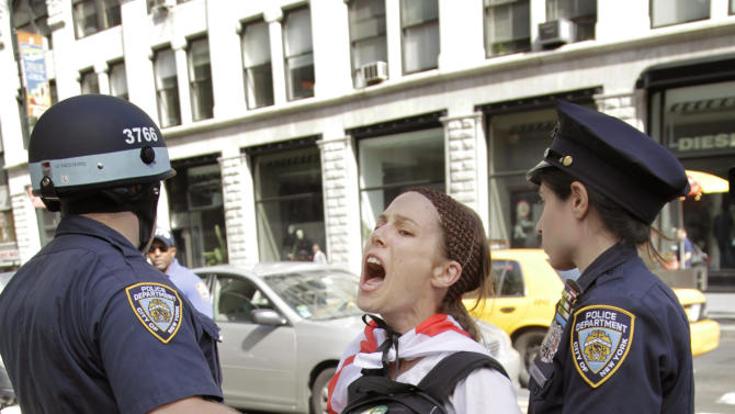 Police take Amanda Lodoza, an activist associated with the Occupy Wall Street movement, into custody during a march in New York, Sunday, Sept. 16, 2012. The Occupy Wall Street movement will mark its first anniversary on Monday. (AP Photo/Seth Wenig)