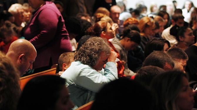 Mourners react during a packed overflow service at Clayton Baptist Church Tuesday, Oct. 23, 2012, in Clayton, N.J., as the small town tries to begin healing after missing 12-year-old Autumn Pasquale was found dead. Her body was found around 10 p.m. Monday, just blocks away from her house. Gloucester County Prosecutor Sean Dalton said two teenage brothers were charged Tuesday with murdering Pasquale, who had been missing since the weekend, prompting a frantic search by her small hometown. (AP Photo/Mel Evans)