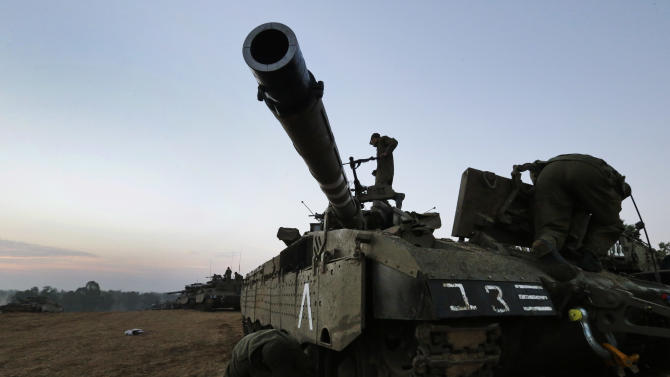 Israeli soldiers work on a tank at a staging area near the Israel Gaza Strip Border, southern Israel, Tuesday, Nov. 20, 2012.  On Tuesday, grieving Gazans were burying militants and civilians killed in ongoing Israeli airstrikes, and barrages of rockets from Gaza sent terrified Israelis scurrying to take cover. Efforts to end a week-old convulsion of Israeli-Palestinian violence drew in the world's top diplomats Tuesday, with U.S. President Barack Obama dispatching his secretary of state to the region on an emergency mission and the U.N. chief appealing from Cairo for an immediate cease-fire. (AP Photo/Lefteris Pitarakis)