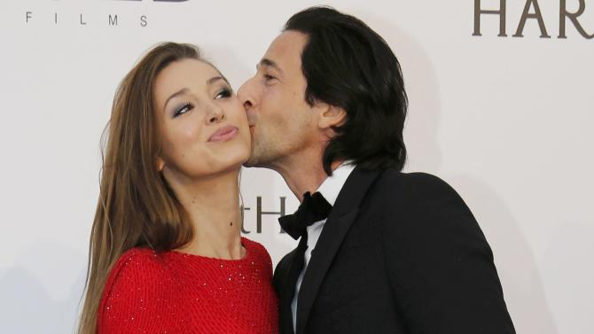 Actor Adrien Brody kisses his partner Lara Lieto as they pose during a photocall at the amfAR's Cinema Against AIDS 2015 event during the 68th Cannes Film Festival in Antibes, near Cannes