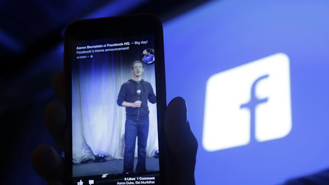 In this Thursday, April 4, 2013, photo, Michael Goodwin, Senior Partner for HTC, displays an HTC First cell phone wit the new Facebook interface at Facebook headquarters in Menlo Park, Calif. Facebook's net income and revenue grew in the first quarter of 2013, helped by an increase in mobile ad revenue, a figure that some skeptical investors have been watching closely. Facebook Inc. said Wednesday that its net income was $219 million, or 9 cents per share, in the January-March period. (AP Photo/Marcio Jose Sanchez)