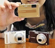 Panasonic employee displays compact digital cameras in Tokyo, 2009. The soaring popularity of smartphones is crushing demand for point-and-shoot cameras, firms scramble to hit back with web-friendly features and boost quality, analysts say