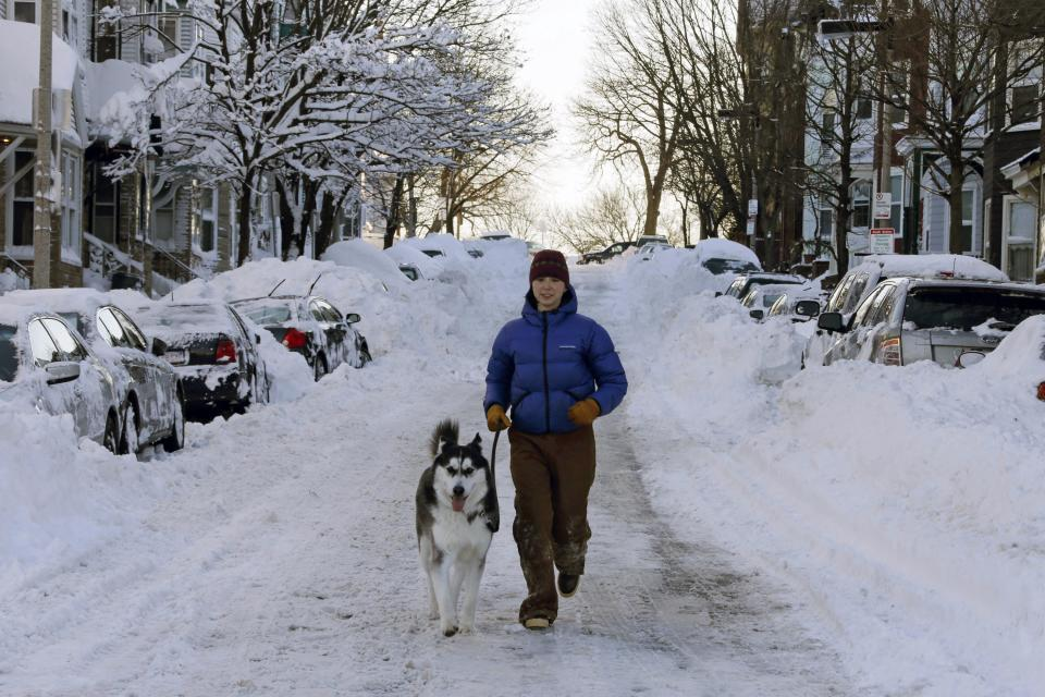Jennifer Renz and her dog Gus run down East Third street in the South Boston neighborhood of Boston early Sunday morning, Feb. 10, 2013 in Boston. (AP Photo/Gene J. Puskar)