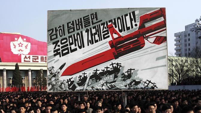 "North Koreans attend a rally to support a statement given on Tuesday by a spokesman for the Supreme Command of the Korean People's Army vowing to cancel the 1953 cease-fire that ended the Korean War as well as boasting of the North's ownership of ""lighter and smaller nukes"" and its ability to execute ""surgical strikes""  meant to unify the divided Korean Peninsula, at Kim Il Sung Square in Pyongyang, North Korea, on Thursday, March 7, 2013. North Korea on Thursday vowed to launch a pre-emptive nuclear strike against the United States, amplifying its threatening rhetoric hours ahead of a vote by U.N. diplomats on whether to level new sanctions against Pyongyang for its recent nuclear test. The billboard in background depicts a large bayonet pointing at U.S. army soldiers with writing reading ""If you dare invade, only death will be waiting for you!"" (AP Photo/Jon Chol Jin)"