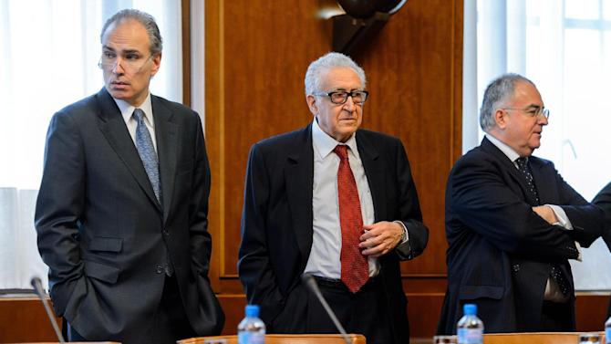 UN-Arab League envoy Lakhdar Brahimi, center, waits with members of his delegation prior to a meeting at the United Nations office in Geneva, Switzerland, Friday, Dec. 20, 2013. Brahimi is meeting with U.S. and Russian delegations to try to agree which nations should be invited to Syria peace talks in Geneva next month. (AP Photo/Fabrice Coffrini, Pool)