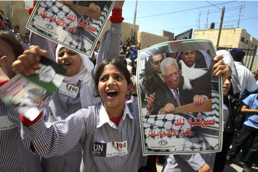 Palestinian schoolchildren hold posters of Palestinian President Mahmoud Abbas during a rally in the West Bank city of Tulkarem, Monday, Sept. 19, 2011. Abbas is set to address the U.N. this week, planning to ask the world to recognize a Palestinian state. Text on poster reads in Arabic: