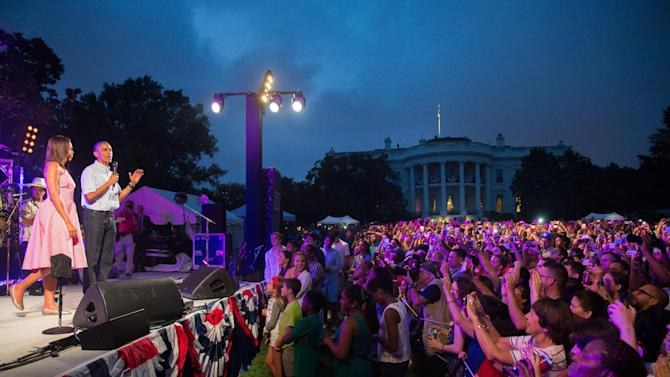 President Barack Obama, accompanied by first lady Michelle Obama, left, delivers remarks during an Independence Day celebration on the South Lawn at the White House in Washington, Saturday, July 4, 2015. (AP Photo/Andrew Harnik)