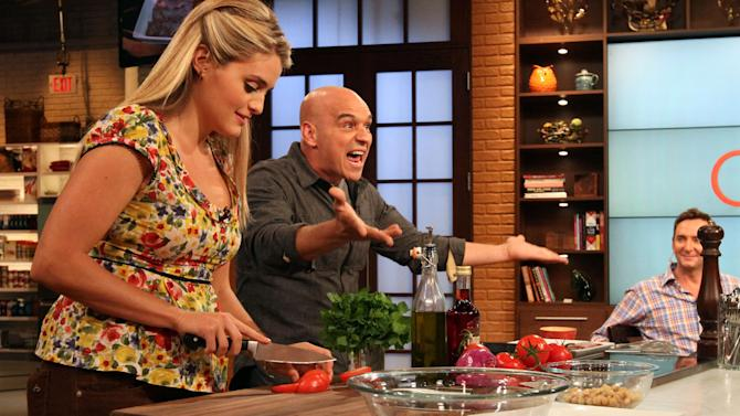 "This Friday, Aug. 26, 2011 photo shows co-hosts Daphne Oz, left, and Iron Chef Michael Symon as they prepare food while Clinton Kelly, right, looks on during a rehearsal of ABC's ""The Chew"" in New York. Can some of food and style TV's biggest stars help ABC soap fans get over cancellation of their favorite stories? The network's counting on it for ""The Chew.""     (AP Photo/Tina Fineberg)"