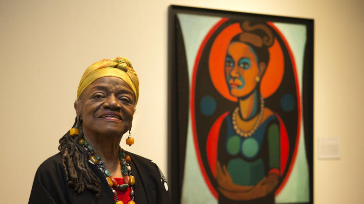 "Artist Faith Ringgold poses for a portrait in front of a painted self-portrait during a press preview of her exhibition, ""American People, Black Light: Faith Ringgold's Paintings of the 1960s"" at the National Museum of Women in the Arts in Washington on Wednesday, June 19, 2013. Ringgold explains her ""confrontational art"" _ vivid paintings whose themes of race, gender, class and civil rights were so intense that for years, no one would buy them. ""I didn't want people to be able to look, and look away, because a lot of people do that with art,"" Ringgold said. ""I want them to look and see. I want to grab their eyes and hold them, because this is America."" (AP Photo/Jacquelyn Martin)"