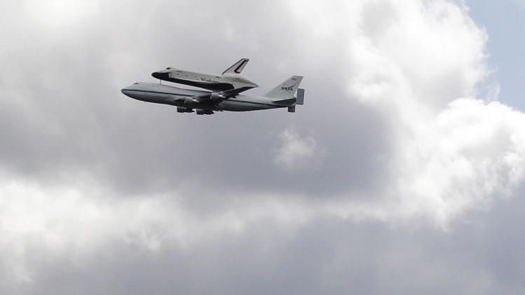 Space shuttle Enterprise, riding on the back of the NASA 747 Shuttle Carrier Aircraft, cruises by the Empire State Building as it makes its way to John F. Kennedy International Airport seen from Union City, N.J., Friday, April 27, 2012. Enterprise is eventually going to make its new home in New York City at the Intrepid Sea, Air and Space Museum. (AP Photo/Julio Cortez)