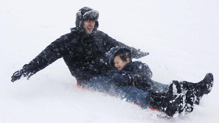 Julian Fischer and his son, Zavoli, 5, take advantage snow by sledding on a hill at Lyndale Farmstead, Sunday, Dec. 9, 2012, in Minneapolis. A major winter storm was expected to dump 9 to 15 inches across a broad belt of central Minnesota including the Twin Cities area by Sunday night, and the storm was also to bring heavy snow to parts of western Wisconsin. (AP Photo/The Star Tribune, Richard Tsong-Taatarii) MANDATORY CREDIT; ST. PAUL PIONEER PRESS OUT; MAGS OUT; TWIN CITIES TV OUT.