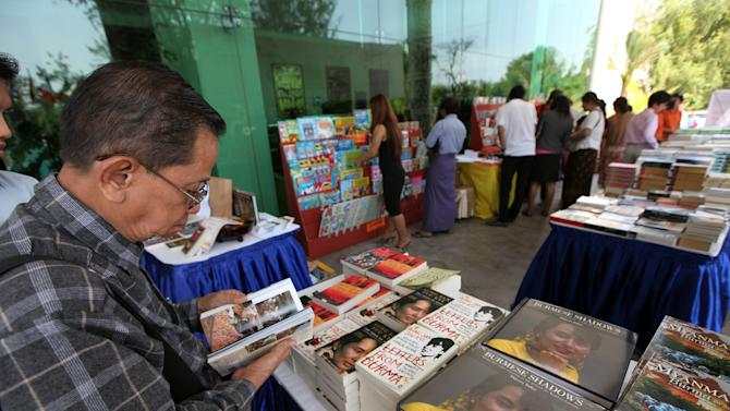 A man browses a book on Myanmar's Nobel Peace Prize laureate Aung San Suu Kyi displayed during the Irrawaddy Literary Festival at Inya Lake hotel Friday, Feb. 1, 2013, in Yangon, Myanmar. The country's first international literary festival opens Friday, featuring dozens of authors from around the world, including Suu Kyi. (AP Photo/Khin Maung Win)