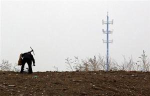 A mobile phone tower is seen behind a man carrying a pick over his shoulder on the outskirts of Beijing