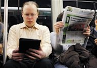 A commuter (L) reads on a Kindle e-reader while riding the subway in Cambridge, Massachusetts March 18, 2011. REUTERS/Brian Snyder