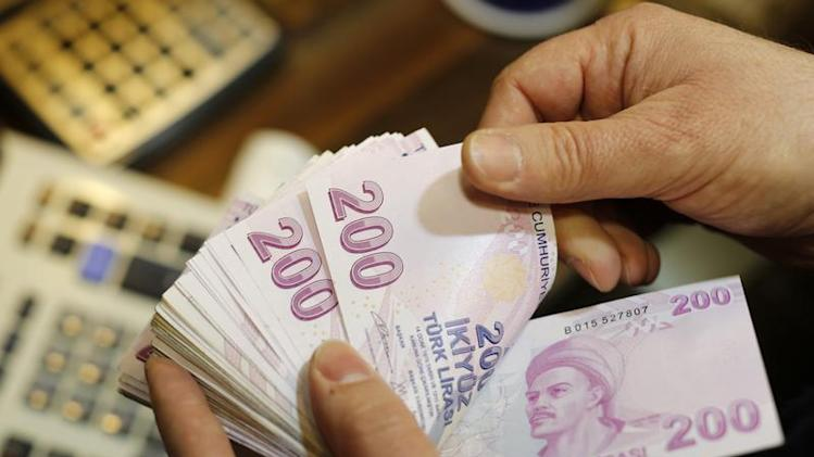 A money changer counts Turkish lira bills at a currency exchange office in Istanbul
