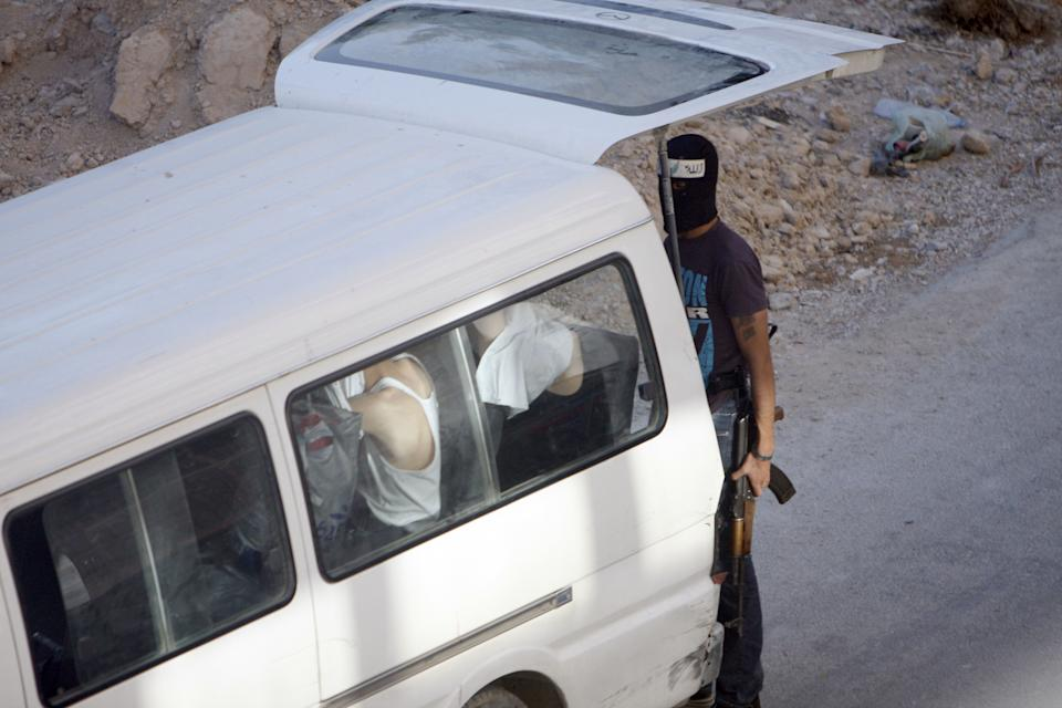 In this Thursday Aug. 2, 2012 photograph,a Syrian rebel fighter stands by a van with people detained at an improvised checkpoint in a suburb of Damascus, Syria. (AP Photo)