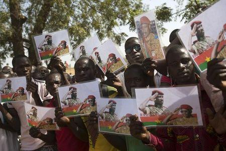 People hold pictures showing former president Thomas Sankara and PM Isaac Zida during funeral service for six people killed during popular uprising of October 30 and 31 in Ouagadougou