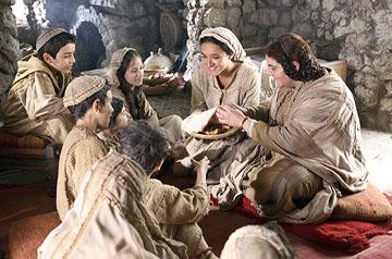 Keisha Castle-Hughes as Mary, bringing food to local children in New Line Cinema's The Nativity Story