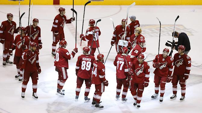 The Phoenix Coyotes players wave their sticks as they acknowledge the crowd after an NHL hockey game against the Dallas Stars on Sunday, April 13, 2014, in Glendale, Ariz.  The Coyotes defeated the Stars 2-1