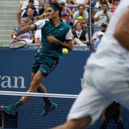 Federer of Switzerland rises in the air as he prepares to hit a smash to Mayer of Argentina during their first round match at the U.S. Open Championships tennis tournament in New York