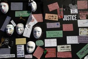 Messages written on papers and masks are displayed on a board along Canfield Drive where Brown was fatally shot by a police officer in Ferguson