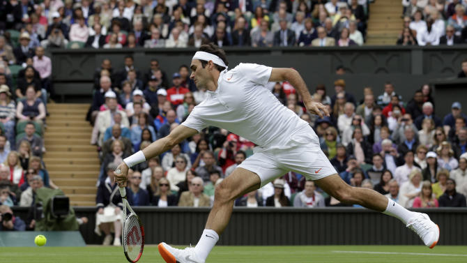 Roger Federer of Switzerland stretches to return the ball to Victor Hanescu of Romania during their Men's first round singles match at the All England Lawn Tennis Championships in Wimbledon, London, Monday, June 24, 2013. (AP Photo/Anja Niedringhaus)