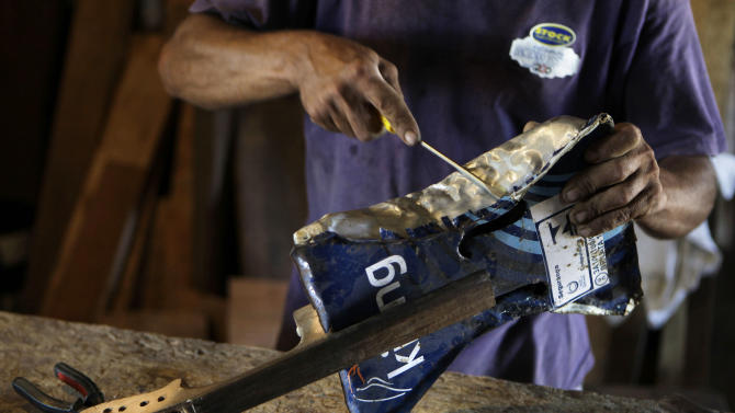 """In this Dec. 11, 2012 photo, Nicolas Gomez makes a violin with recycled materials at his home in the Cateura, a vast landfill outside Paraguay's capital of Asuncion, Paraguay. Gomez, a trash picker and former carpenter, was asked by Favio Chavez, the creator of  ìThe Orchestra of Instruments Recycled From Cateura,"""" to make instruments out of materials from the dump to help keep the younger kids occupied.  ìI only studied until the fifth grade because I had to go work breaking rocks in the quarries,î said Gomez, 48. (AP Photo/Jorge Saenz)"""