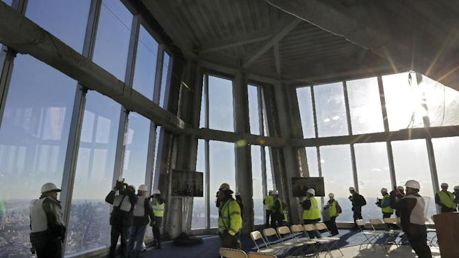 Members of the media tour the unfinished observation deck on the 100th floor of the One World Trade Center building, under construction in New York, Tuesday, April 2, 2013. The observation deck will occupy the tower's 100th through 102nd floors. Elevators will whisk visitors to the top in just one minute but the experience of visiting the attraction will take an hour. (AP Photo/Richard Drew)