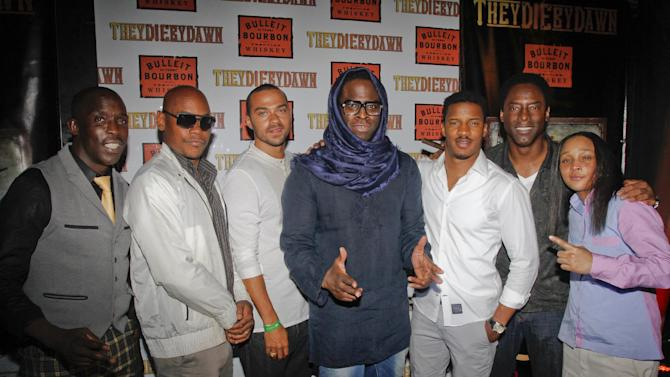 """IMAGE DISTRIBUTED FOR BULLEIT BOURBON - Director Jeymes Samuel, center, is joined by cast members Michael K. Williams, Bokeem Woodbine, Jesse WIlliams, Nate Parker, Isaiah Washington and Felicia Pearson, left to righ, on the red carpet at the Bulleit Bourbon presents """"They Die by Dawn"""" premiere at SXSW, on Saturday, March 16, 2013 in Austin, Texas. (Photo by Jack Plunkett/Invision for Bulleit Bourbon/AP Images)"""