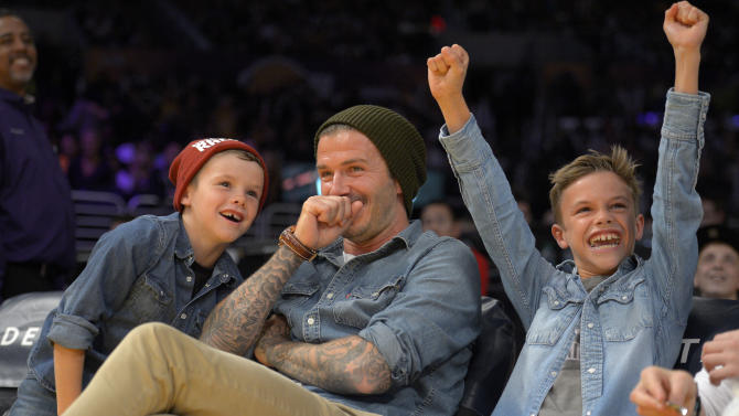 Soccer player David Beckham, center, laughs as his son Romeo, right, cheers while his other son Cruz looks on as they watch the Los Angeles Lakers play the Phoenix Suns in their NBA basketball game, Friday, Nov. 16, 2012, in Los Angeles. The Lakers won 114-102. (AP Photo/Mark J. Terrill)